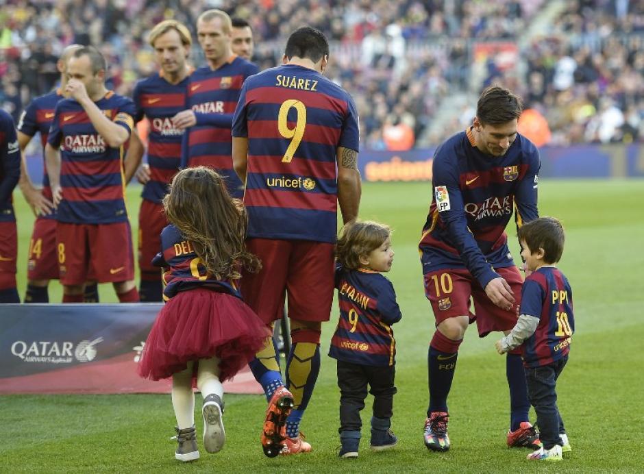 Lionel Messi camina con su hijo Thiago Messi y el uruguayo Luis Suárez entra a la cancha con Benjamin y Delfina, sus dos hijos. (Foto: AFP)