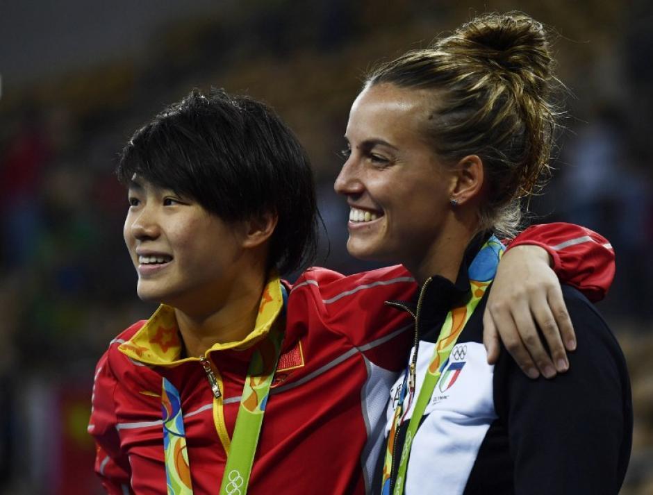 Las otras dos medallistas vieron la romántica escena en primer plano. (Foto: AFP)