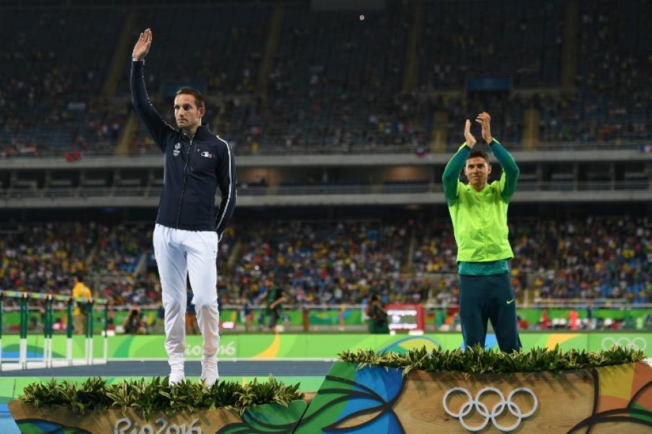 Su rival y medallista de oro, Thiago Braz, cuando pide aplausos para Lavillenie. (Foto: AFP)