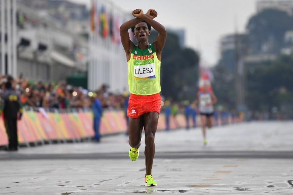 Con este gesto entró Feyisa Lilesa a la meta. (Foto: AFP)