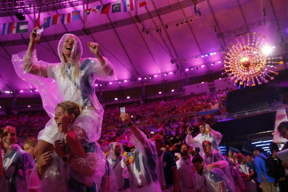 Los atletas tuvieron que salir con capas, por la lluvia. (Foto: AFP)