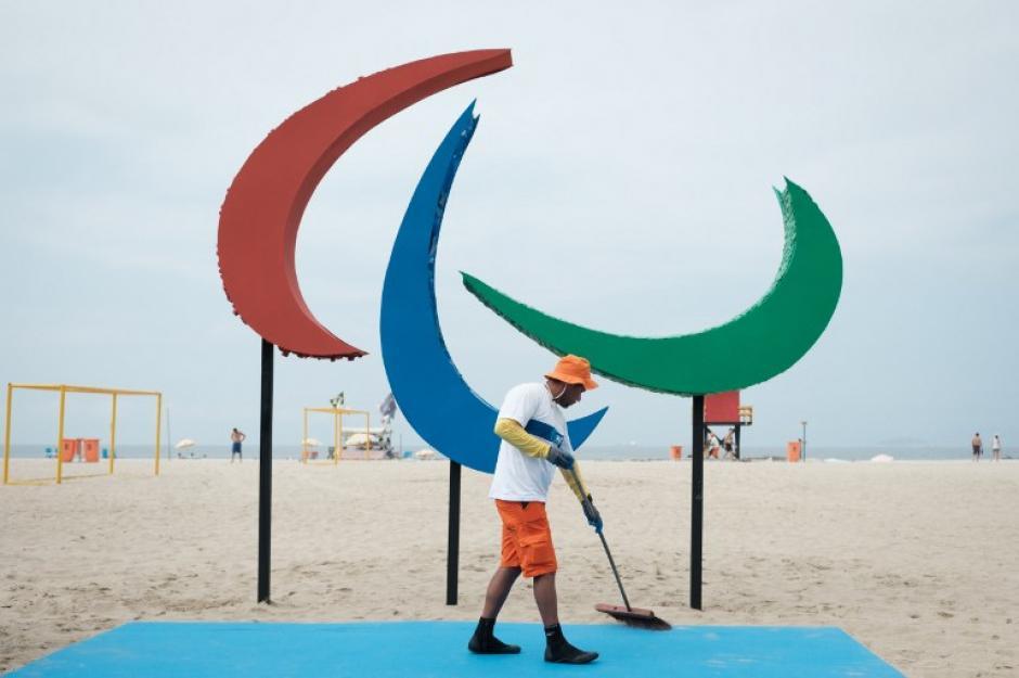 Un voluntario barre la base del símbolo de los Juegos Paralímpicos. (Foto: AFP)
