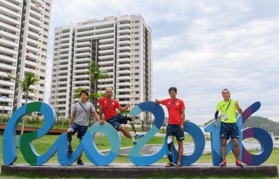 Varios atletas japoneses posan frente a la Villa Olímpica. (Foto: AFP)