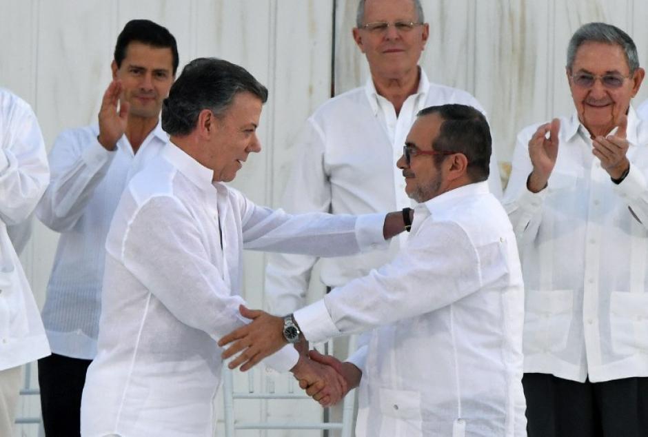 Luego de que se firmaran los acuerdos de paz, Santos y Londoño se dan la mano. (Foto: AFP)