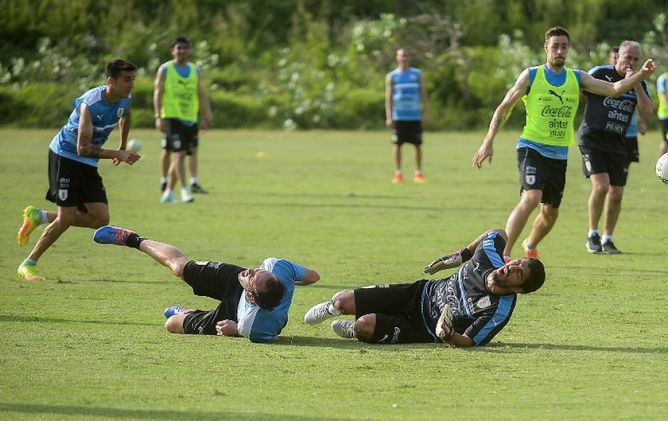 Suárez y Godín, con gestos de dolor después del choque. (Foto: AFP)