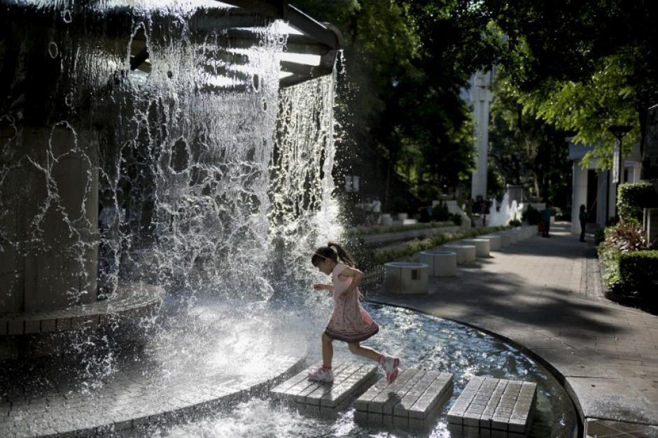 Una joven se refresca en una fuente en un día caluroso de verano en Hong Kong. El Observatorio de Hong Kong emitió una advertencia de clima caliente ya que las temperaturas alcanzaron los 34 grados centígrados (93 grados Fahrenheit) en la ciudad del sur de China. (Foto: AFP/ALEX OGLE)