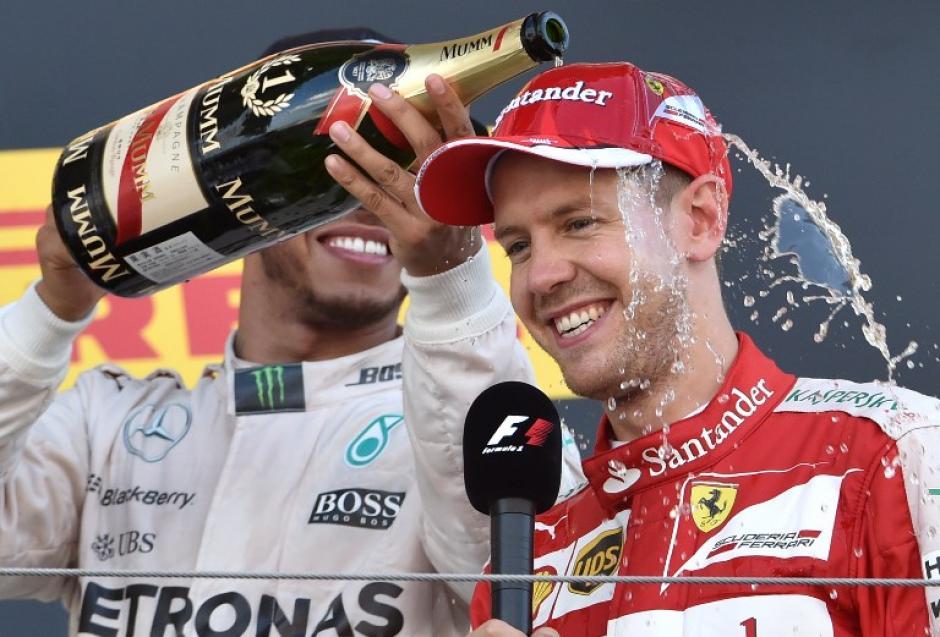 Hamilton rocía de champaña a Sebastian Vettel. (Foto: AFP)