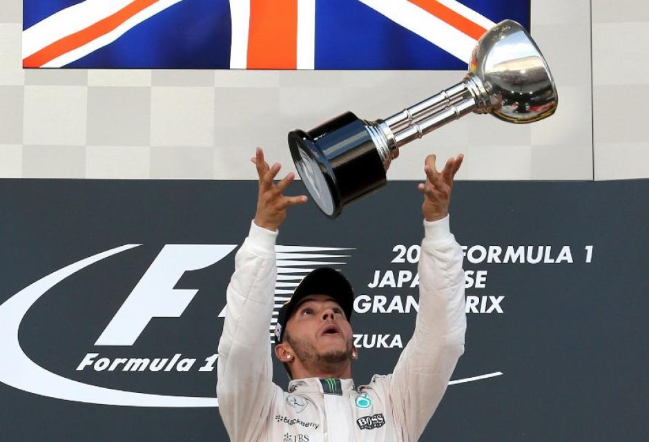 Hamilton juega feliz con el trofeo ganado en Japón. (Foto: AFP)