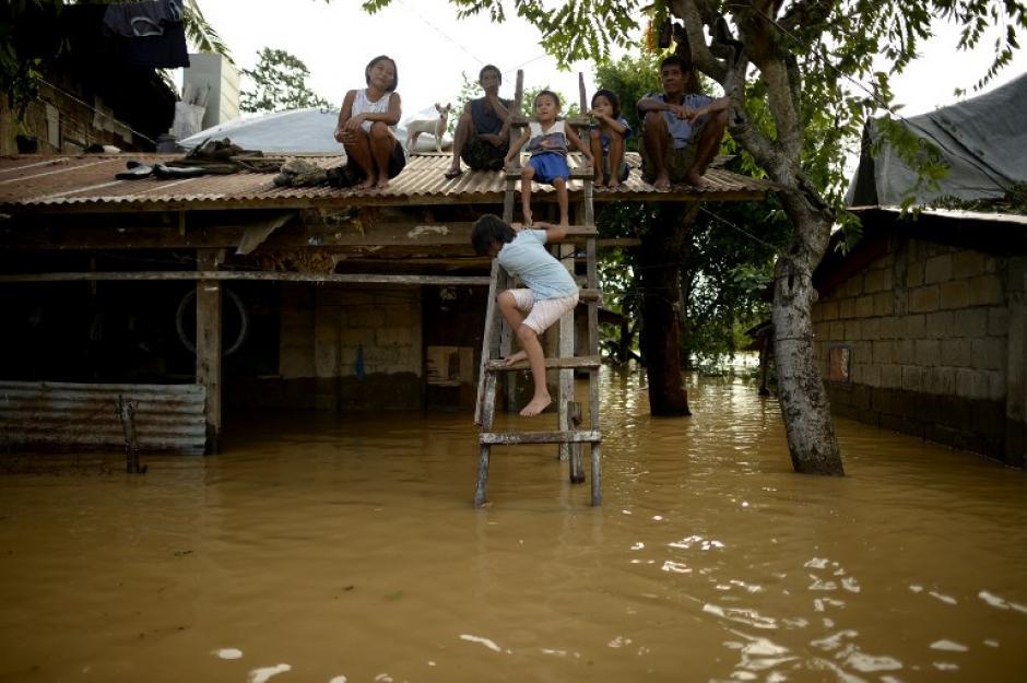 Los residentes afectados por las inundaciones esperan en su casa ser auxiliados en Barangay Camanutan, provincia de Isabela, al norte de Manila el 19 de octubre de 2015, un día después de que el tifón Koppu sacudió la provincia de Aurora. (Foto: AFP)