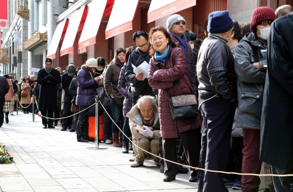 """Compradores japoneses hacen cola fuera de una tienda por departamentos, ya que esperar para entrar con la esperanza de recoger """"bolsas de la suerte"""" que contienen artículos por valor de tres veces su precio, durante una venta para celebrar un nuevo año de negocios. Foto: AFP/YOSHIKAZU TSUNO)"""