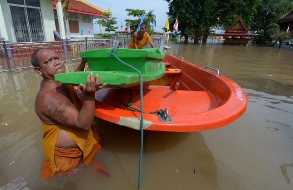 monjes budistas llevan un barco a través de las aguas de inundación en un templo en la provincia de Ayutthaya, al norte de Bangkok.