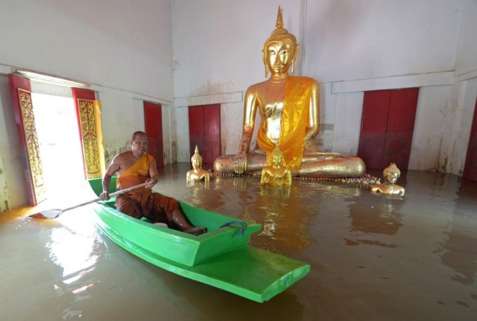 Un monje budista rema en un barco frente a una estatua de Buda en un templo en la provincia de Ayutthaya, al norte de Bangkok.