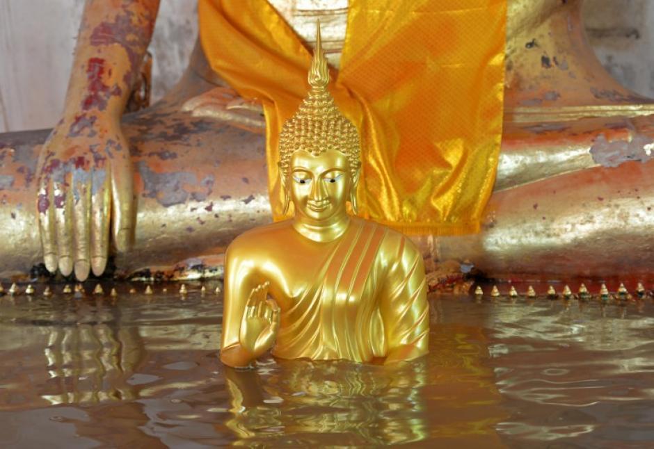 Una estauta de Buda es cubierta por el agua, después de las torrenciales lluvias que dejaron cientos de damnificados.