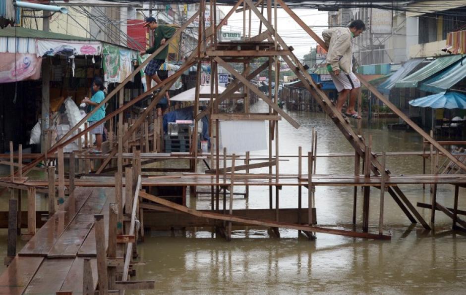 Aldeanos tailandeses utilizan un puente de madera para caminar sobre las aguas de inundación en un mercado en la provincia de Ayutthaya, al norte de BangkoK.