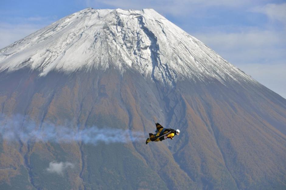"""El piloto suizo Yves Rossy, o """"Jetman"""", vuela cerca del monte Fuji. Las alas a potencia del aviador suizo le han permitido sobrevolar algunos de los lugares más impresionantes del mundo, con un equipo de 132 libras atado a la espalda. Breitling SA/Proyecto Jetman/ Katsuhiko TOKUNAGA/AFP"""