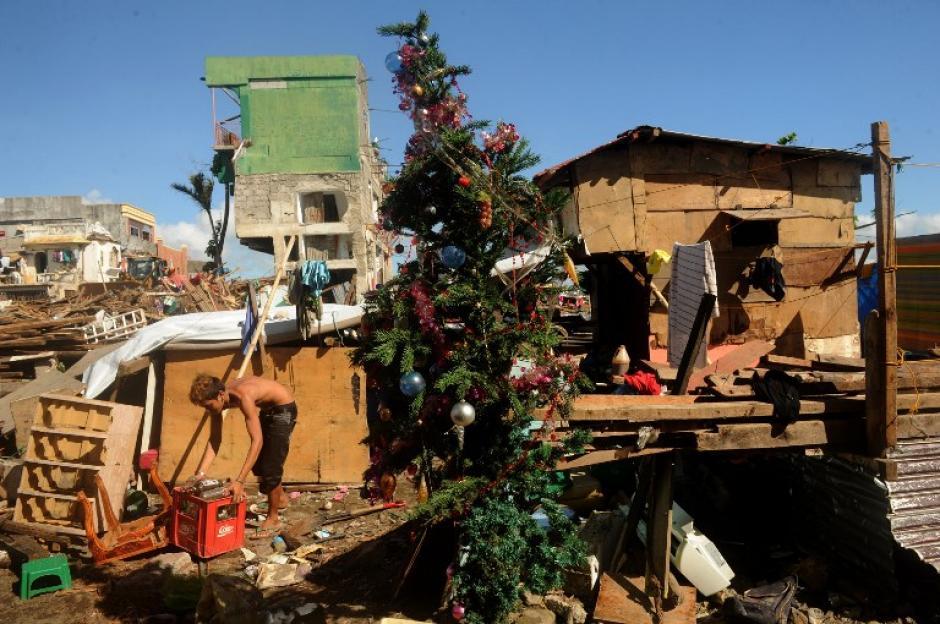 Un hombre recopila materiales recuperables entre los escombros de las casas destruidas en Tacloban, provincia de Leyte, en Filipinas, frente a un árbol de Navidad erigido entre el desastre que dejó el tifón Haiyan. (Foto: AFP)