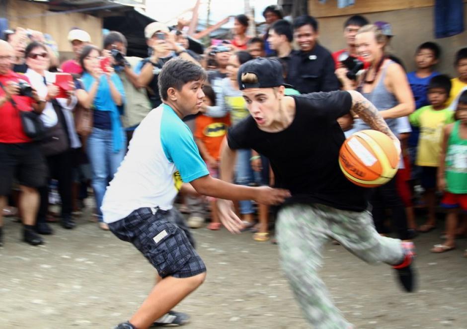 Luego de cantar, el joven canadiense jugó pelota con los niños de Filipinas. (Foto: AFP)