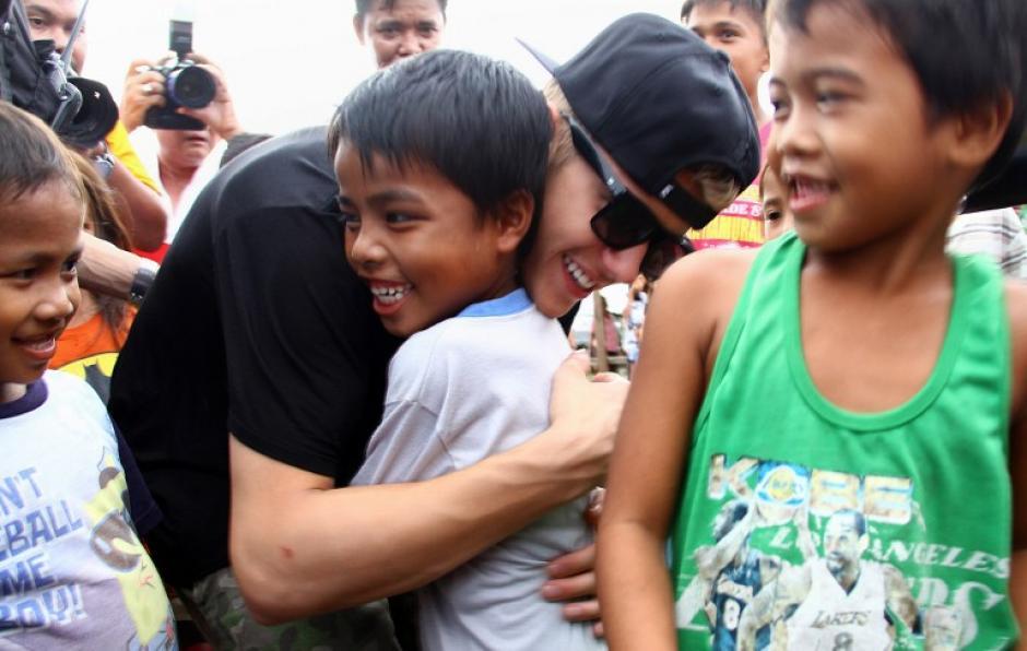 """""""Verdadera felicidad"""" es como tituló Justin la fotografía donde abraza a un pequeño de Filipinas. (Foto: AFP)"""