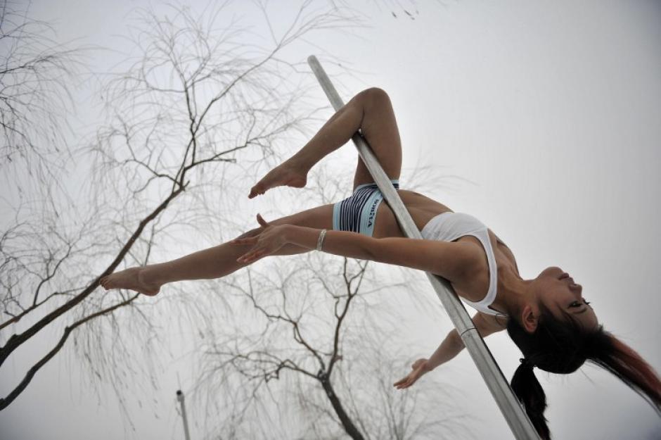 Estudiantes del Centro de Formación de Danza China llevaron a cabo una presentación de Pole Dance en el Parque Acuático de Tianjin. (AFP)
