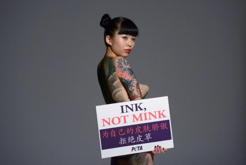 """Wang Ke, una artista del tatuaje chino, muestra sus tatuajes mientras sostiene un cartel que dice, """"Tinta, no visón"""" en referencia al uso de piel de animal para vestuarios. """"Siéntase orgulloso de su propia piel, no use pieles"""" indica, durante una sesión de publicidad para el grupo de derechos de los animales PETA (Personas por el Tratamiento Ético de los Animales) en Pekín. Wang muestra a los tatuajes como una alternativa al uso de pieles, en la imagen del 6 de enero tomada por el fotógrafo de AFP Wang Zhao."""