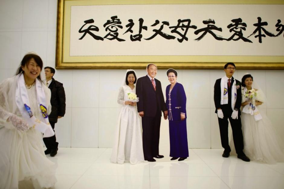 Las parejas se toman fotografías con los retratos del líder de la secta Moon, Sun Myung Moon y su esposa. Foto AFP