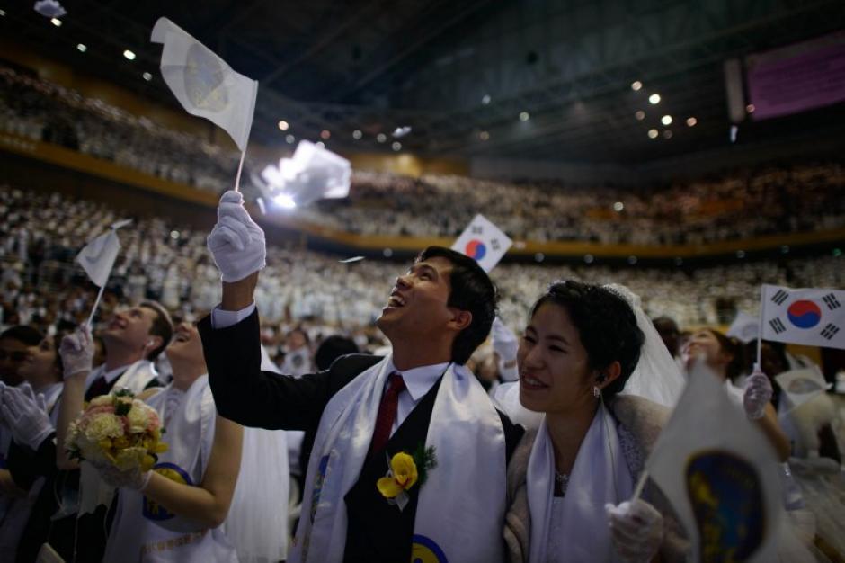 Las parejas ya ubicadas en la Unification Church, sede de la boda colectiva y ondeando la bandera de Corea del Sur. Foto AFP