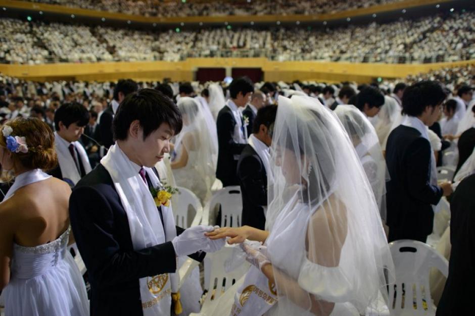 Las parejas colocándose el anillo de matrimonio. Foto AFP