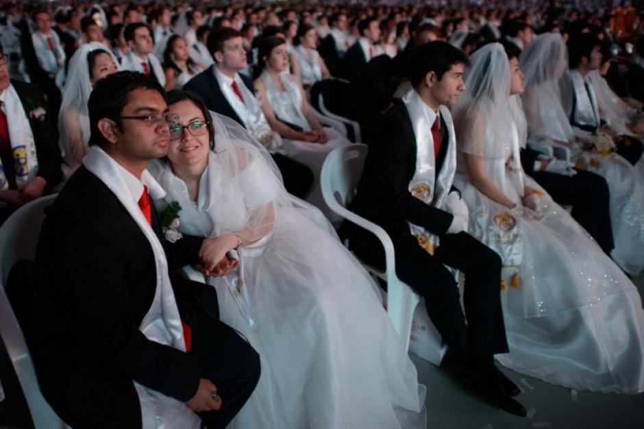 Las parejas participantes escuchando la ceremonia. Foto AFP
