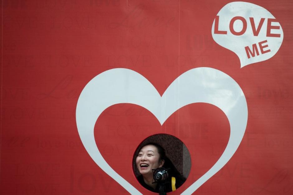 Una mujer sonríe y posa para tomarse una fotografía, ante un puesto de fotos que se instaló en un centro comercial de Hong Kong que promociona regalos y compras para el Día de San Valentín. Foto AFP