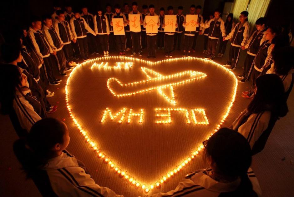 Esta imagen tomada en 10 de marzo 2014 muestra a estudiantes que oran por los pasajeros de los desaparecidos del vuelo de Malaysia Airlines. (Foto: AFP)
