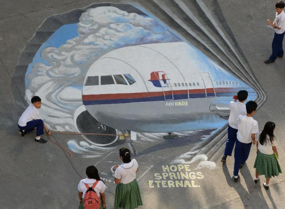 Estudiantes pasan junto a un mural gigante del vuelo de Malaysia Airlines MH370, en el distrito financiero de Makati en Manila, Filipinas. Creado como una acción de solidaridad por un grupo de artistas. (Foto: AFP)
