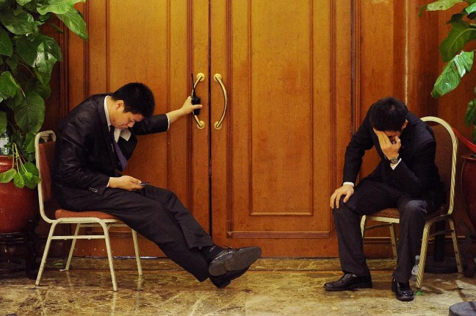 Dos agentes de seguridad se sientan en la entrada de un salón del hotel, donde los familiares de los pasajeros de los desaparecidos del vuelo de Malaysia Airlines esperaban noticias. (Foto: AFP)