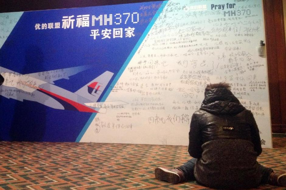 Una mujer permanece sentada frente a un tablero lleno de oraciones y mensajes escritos por los familiares de los pasajeros desaparecidos en la sala de reuniones del hotel de Lido, en Beijing. (Foto: AFP)