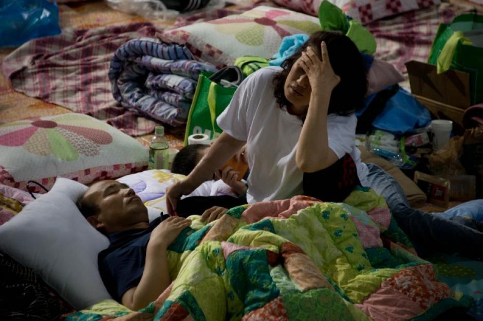 Un familiar de una víctima del barco hundido Sewol, permaence en un gimnasio esperando información. (Foto: AFP)
