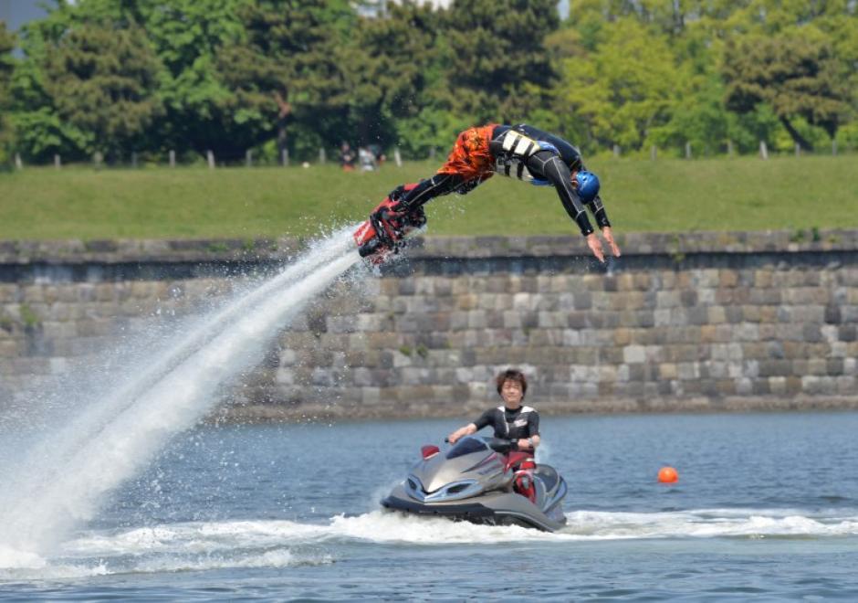 """Un japonés muestra la Flyboard, que es propulsada con agua con un mecanismo de mangueras especial, durante el Festival de Deportes de Odaiba Beach. En este se disfrutaron distintos deportes de playa y náuticos en un evento llamado la """"Semana Dorada"""" en Tokio, Japón. La foto del día 5 de mayo fue tomada por Yoshikazu Tsuno de AFP."""