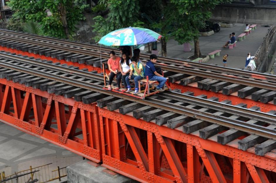 En Filipinas pequeños propietarios de carritos utilizan los rieles del tren para cobrar pequeñas tarifas por transporte a cortas distancias. Con este servicio obtienen una media de aproximadamente 6,75 dólares por día, a pesar de la potencial amenaza a la que se enfrentan desde que los trenes también utilizan los rieles. (Foto: AFP)