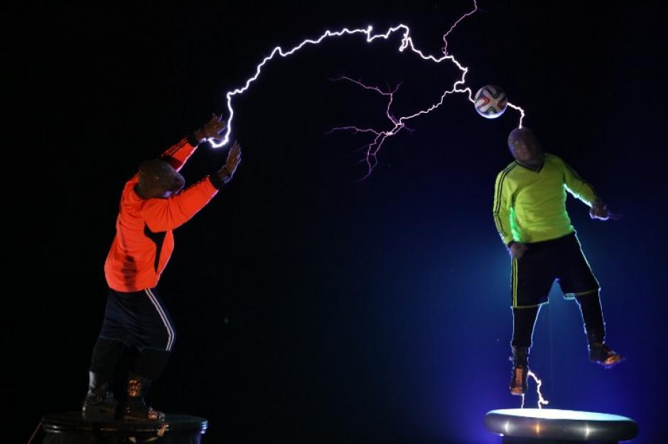 El grupo de performance china LightningFan muestra los miembros del grupo Wang Hongbin (Derecha) y Lin Hongru realizar con una pelota de fútbol, ya que crean un rayo con una bobina de Tesla en Changle, provincia de Fujian del este de China . La bobina de Tesla inventada por Nikola Tesla en 1891 es un transformador que produce grandes cantidades de tensión a altas frecuencias que crea largos rayos de electricidad como un rayo. La foto del día fue tomada por el fotógrafo de AFP Wang Hongxin.