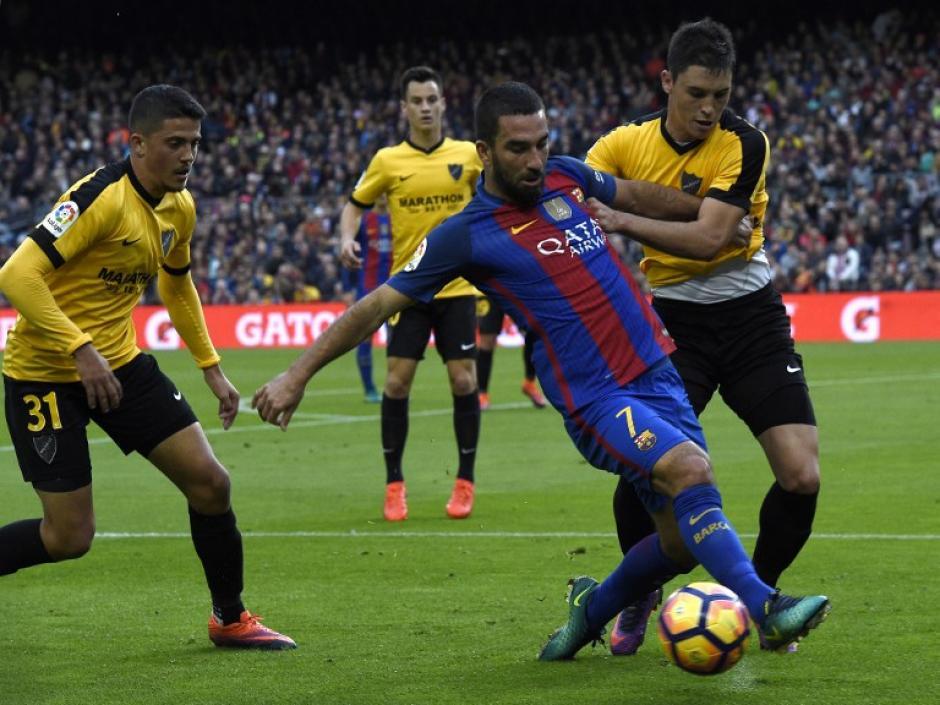 Arda Turan tampoco pudo contra una defensiva del Málaga (Foto: LLUIS GENE/AFP)
