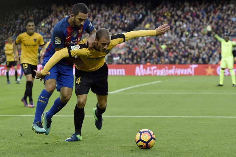 Y la defensa de Málaga a pesar de quedarse con diez hombres en la cancha sacó un valioso empate de visita. (Foto: LLUIS GENE/AFP)