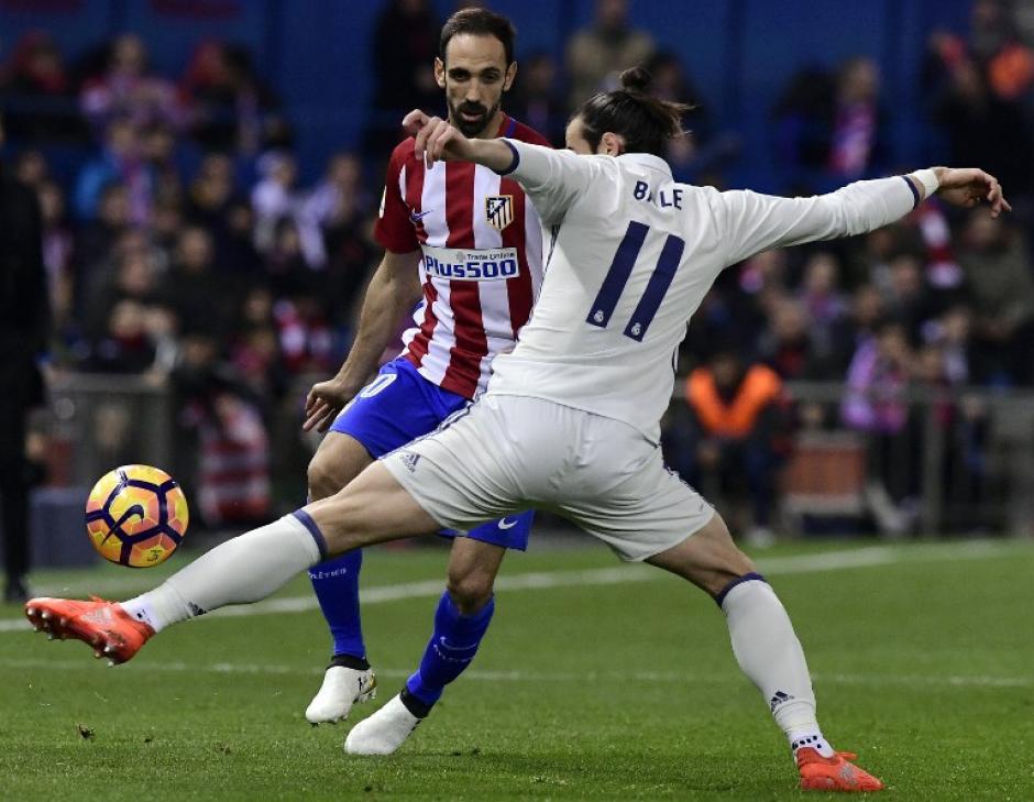 El jugador del Real Madrid, Gareth Bale disputa la pelota ante la llegada de Juanfra del Atlético del Madrid. (Foto: GERARD JULIEN/AFP)