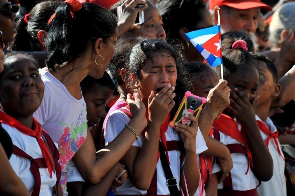 Un grupo de escolares llora cuando pasa frente a ellas la caravana que acompaña a Castro. (Foto: AFP)