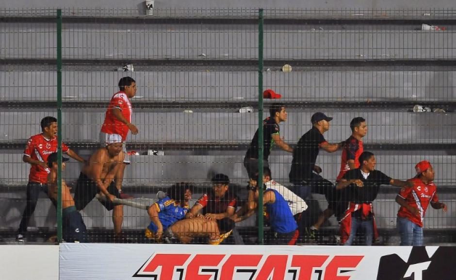 Los aficionados se enfrentaron en los graderíos al finalizar el encuentro. (Foto: AFP)