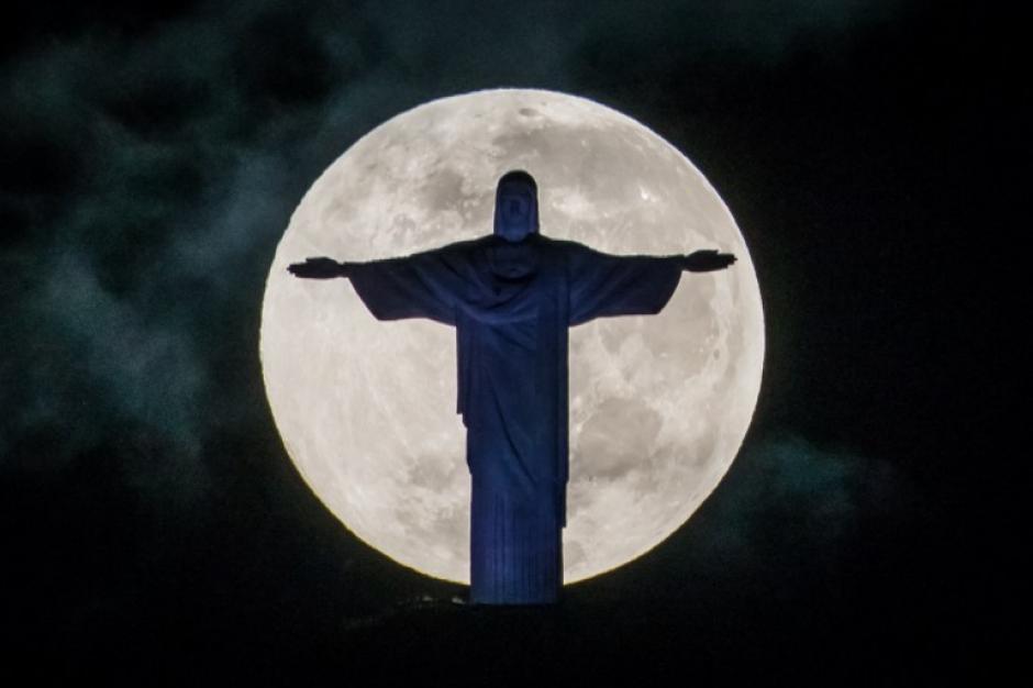 La luna llena detrás de la estatua del Cristo Redentor en la cima del Corcovado en Río de Janeiro durante la visita del Papa Francisco en la Jornada Mundial de la Juventud que se llevó a cabo del 23 al 28 de julio del 2013. AFP/Yasuyoshi CHIBA)