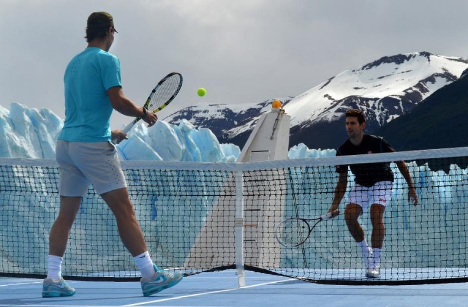 Los tenistas Rafael Nadal de España y Novak Djokovic de Serbia, juguegan al tenis en una cancha flotante cerca del glaciar Perito Moreno (al fondo), cerca de El Calafate, en el patagónica provincia de Santa Cruz, unos 2.750 kilometros al suroeste de Buenos Aires, Argentina, en la foto del 23 de noviembre. (Foto: Ministerio de Turismo de Argentina)