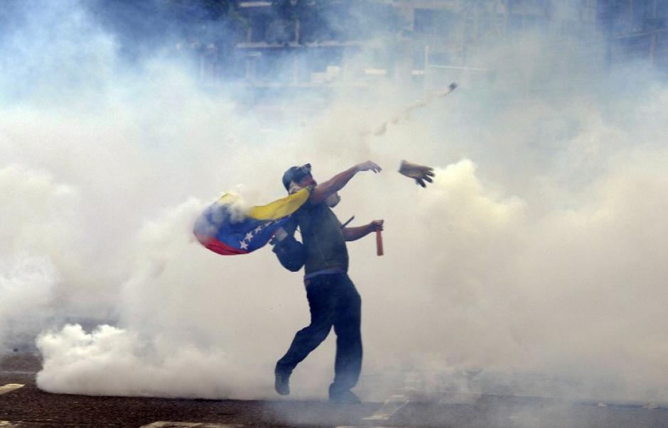 Un manifestante lanza piedras a los policías antidisturbios durante una protesta contra el gobierno en el este de Caracas. Duelo de manifestantes a favor y en contra del gobierno han estado tomando a las calles desde el 4 de febrero en un signo de la profunda polarización. (Foto: AFP/Juan Barreto)