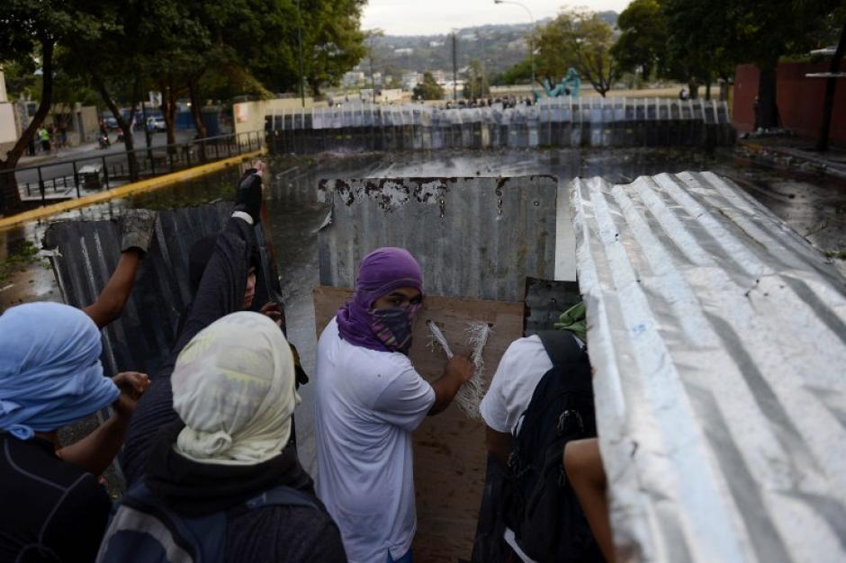 Los manifestantes se enfrentan a policías antidisturbios durante una protesta contra el gobierno en Caracas. Cientos de personas se manifestaron en la capital para denunciar decenas de violaciones de derechos humanos por la policía antidisturbios durante las protestas contra el gobierno que ya dejaron 18 muertos. (Foto: AFP / Leo Ramirez)