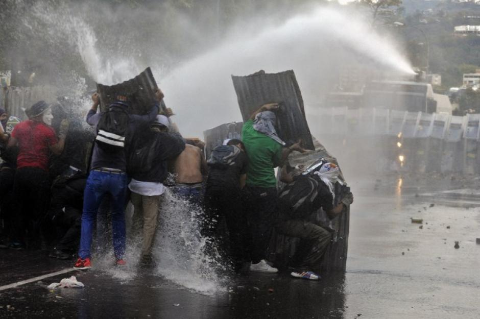 Los manifestantes se protegen detrás de láminas y se enfrentan a la policía antidisturbios durante una protesta contra el gobierno en Caracas. (Foto: AFP/Leo Ramirez)