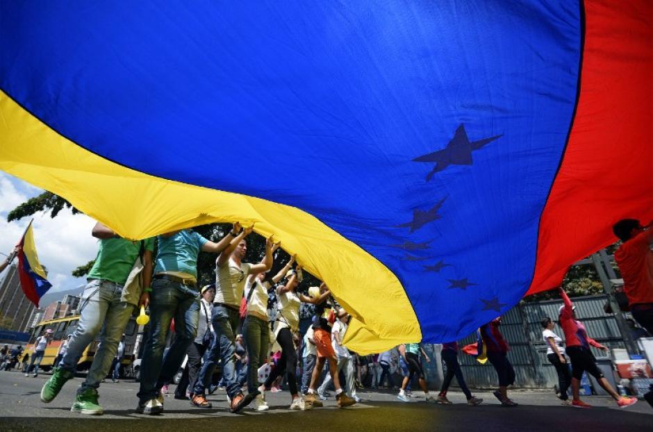 Los manifestantes protestaron con una enorme bandera de Venezuela. (Foto: AFP)
