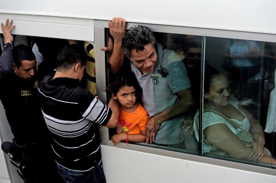 Un agente policial acompaña el recorrido de un bus sobrecargado en la capital salvadoreña.(Foto: AFP)