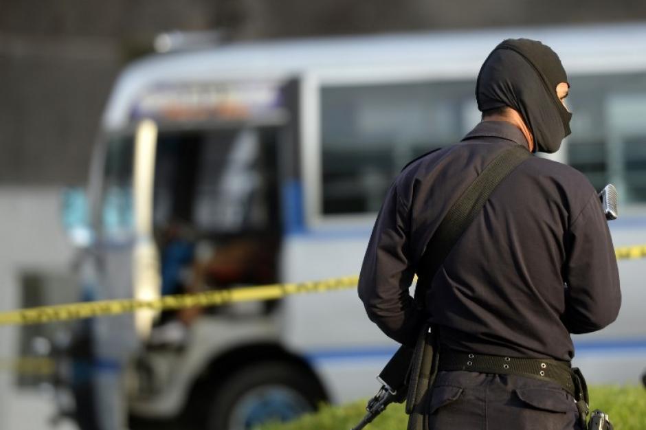 Un policía con el rostro cubierto vigila el lugar donde un conductor falleció luego de ser atacado aparentemente por pandilleros. (Foto: AFP)